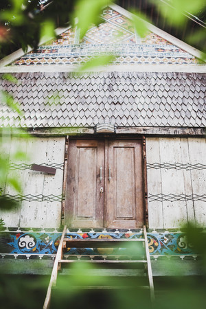 Old wooden traditional house with tile roof, painted walls with ornament and closed shutters door