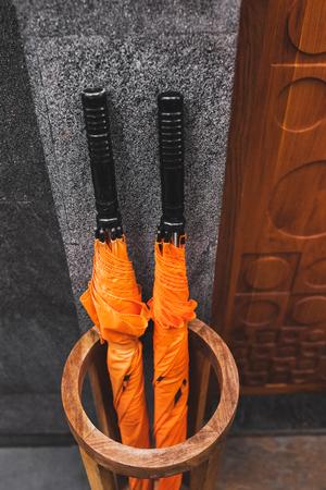 Two orange umbrellas in wooden basket outside room hotel. Resort service
