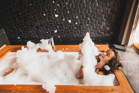 Happy woman playing with foam in big bath with wooden edge. Relaxation in spa Standard-Bild