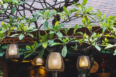 Many beautiful hahdmade wicker lamps hanging outside in garden on tree