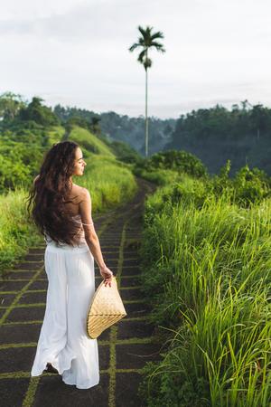 Young beautiful woman walking on Campuhan Ridge way of artists, in Bali, Ubud. Beautiful calm sunny morning 版權商用圖片 - 105545684