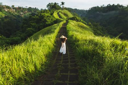 Young beautiful woman walking on Campuhan Ridge way of artists, in Bali, Ubud. Beautiful calm sunny morning