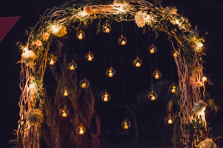 Night wedding ceremony, arch on party decorated with lights and candles in round glass spheres