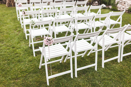 Cozy rustic wedding ceremony with wooden white chairs on green grass
