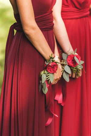 Blumenarmbänder mit roten Rosen und Seidenbändern. Brautjungfern in roten Kleidern, Hochzeit im amerikanischen Stil Standard-Bild