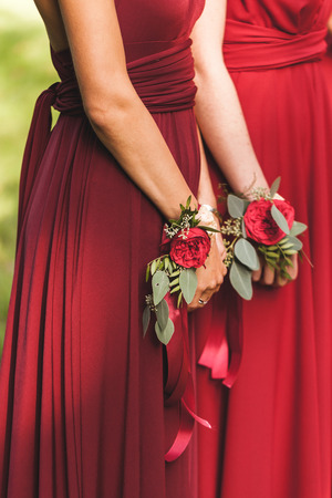 Flower bracelets with red roses and silk ribbons. Bridesmaids in red dresses, american style wedding
