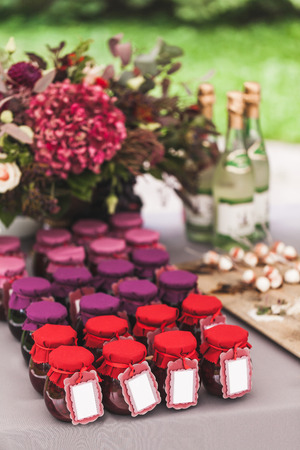 Many craft colorful jars with homemade jam on wedding reception table, gifts for guests