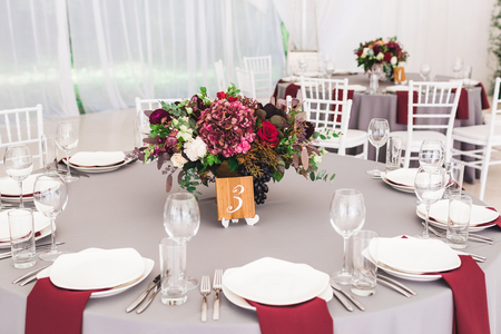 Wedding table, decorated with red flowers bouquets, candles, grey tablecloth, and white plates Stock Photo - 106519730