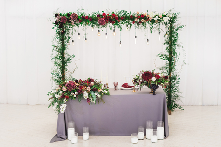 Wedding table, decorated with red flowers bouquets, candles, grey tablecloth, and white plates