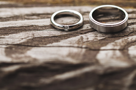 Couple of wedding rings with diamond close up on shabby wooden texture