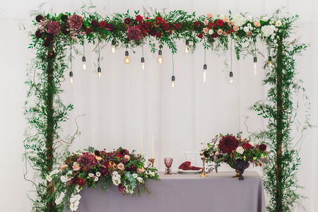 Wedding reception decoration with different electric edison lamps and fresh red and bordo flowers, rustic style Standard-Bild - 106521620