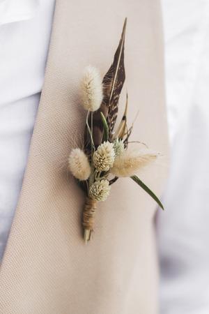 Bräutigam Boutonniere mit Federn und getrockneten Wildblumen im Boho-Stil auf beiger Weste