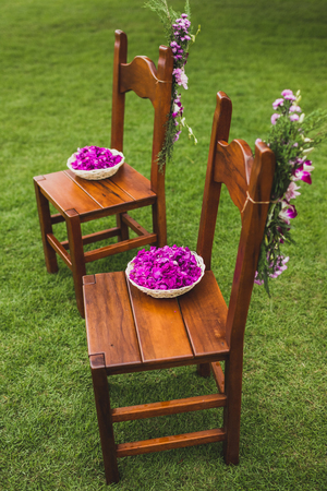 Brown wooden chairs standing on grass on wedding ceremony decorated with pink and purple flowers. Plate with flower petals