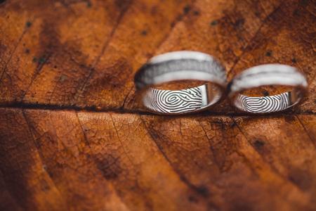 Fedi nuziali con il primo piano delle impronte digitali sulla struttura dello scheletro del foglio di autunno marrone bagnato