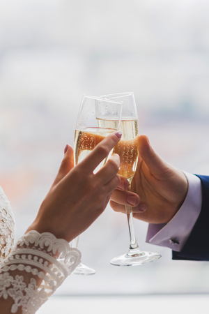Man and woman hands holding two champagne glasses decorated with flowers for wedding ceremony Stock Photo