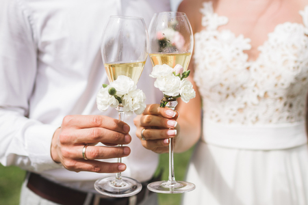 Man and woman hands holding two champagne glasses decorated with flowers for wedding ceremony Фото со стока