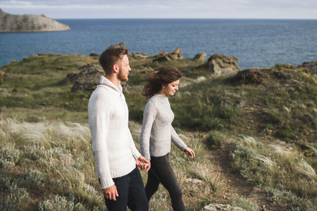 Young couple walking on nordic sea coast with mountain view in spring, casual style clothing sweaters and jeans Stock Photo