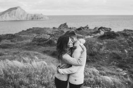 Young couple walking on nordic sea coast with mountain view in spring, casual style clothing sweaters and jeans. Black and white toning 스톡 콘텐츠