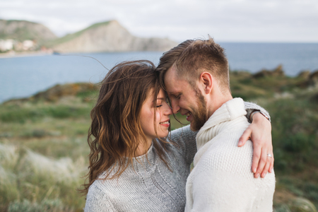 Young couple walking on nordic sea coast with mountain view in spring, casual style clothing sweaters and jeans 스톡 콘텐츠