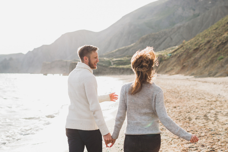 Man and woman in love enjoying together near sea, running by the beach, laughing, kissing and hugging