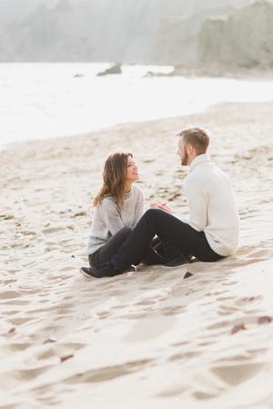 Happy man and woman sitting on sand near sea, romantic mood