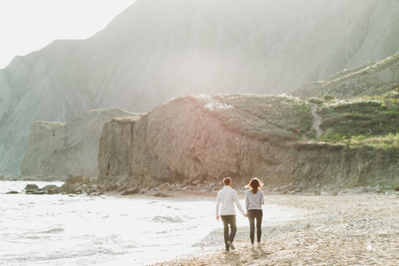 Couple walking by empty sand beach with amazing mountain view with rocks and green hills. Nordic nature 스톡 콘텐츠
