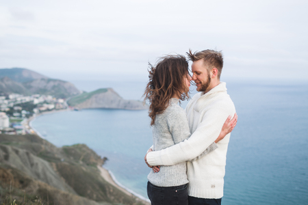 Close-up portrait of couple with wind in hair, hugging and happy together. Both in sweaters