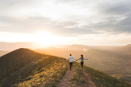 Young couple running together by sunset hill with amazing mountain view 스톡 콘텐츠
