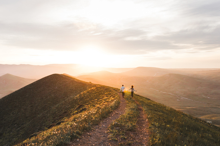 Young couple running together by sunset hill with amazing mountain view Stock Photo