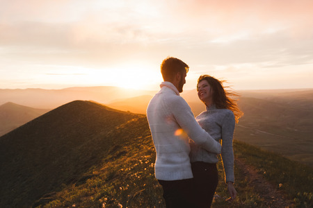 Happy couple hugging and kissing at sunset witn amazing mountain view. Warm evening sun light