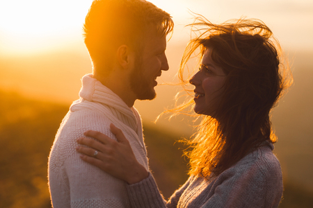 Gentle close-up portrait of man and woman together, happy, looking at each other. Silhouette at beautiful sunset light, wind in hair