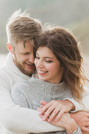 Close-up portrait of man and woman together, happy, looking at each other. Smiling, kissing and laughing
