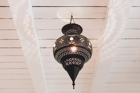 Old vintage lamp in moroccan style hanging on white wooden roof