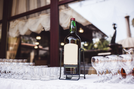 White table with lot of empty glasses and whisky bottle on stand. Wedding party reception