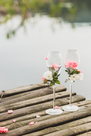 Two decorated champagne glasses with rose flowers on wedding ceremony outdoors