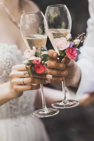 Two decorated champagne glasses in couple hands together