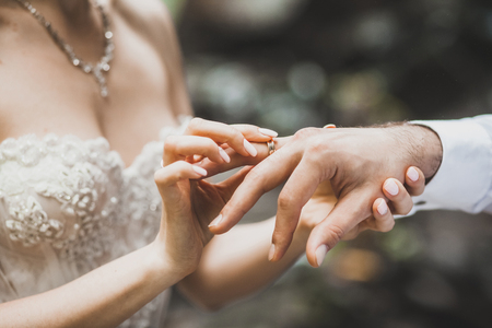 Bride putting ring on groom hand close-up 스톡 콘텐츠