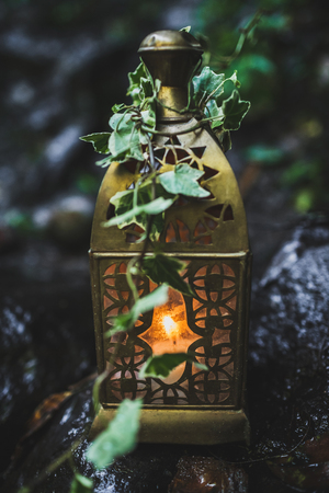 Vintage bronze lamp with candle inside, decorated with ivy on wedding ceremony