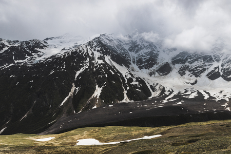 Panoramic view of high mountain peaks in snowy and foggy cold weather. Hiking and climbing in Elbrus region
