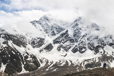 Panoramic view of high mountain peaks in snowy and foggy cold weather. Glacier Semerka, Elbrus region 스톡 콘텐츠