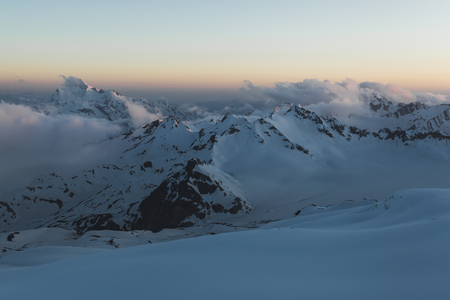 Panoramic view of high mountain peaks in twilight. Hiking and climbing in Elbrus region