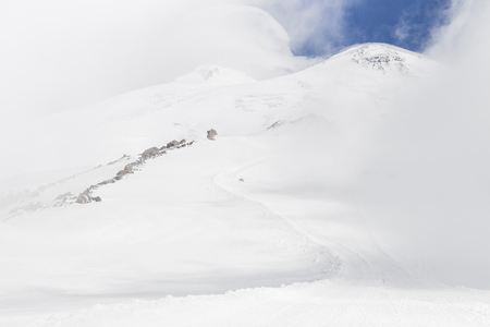 Panoramic view of two Elbrus peaks in snowy and foggy weather. Mountain hiking