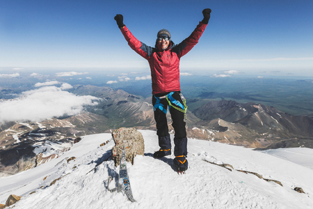 Happy man on top of Elbrus mountain. Winter hiking, achieving the goal