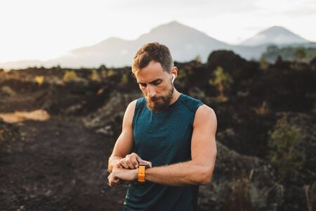Runner checking training results on smart watch. Male athlete using fitness tracker. Stock Photo