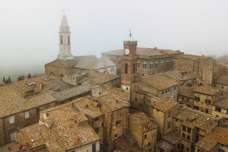Aerial view of ancient italian town Pienza in Tuscany. Tile brown roofs, old town hall, narrow streets and church. Banco de Imagens