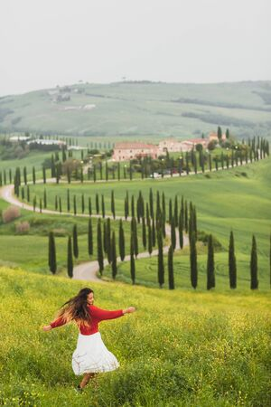 Young happy woman in red sweater and white skirt on background on spring Tuscany landscape. Dancing and enjoying view of cypress alley and yellow flowers field Banco de Imagens