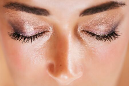 Festive glowing eyeshadow make up in brown and pink colors with shiny and glitter sparkles close up. Beauty trendy concept.
