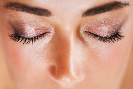 Maquillaje de sombra de ojos brillante festivo en colores marrón y rosa con destellos brillantes y purpurina de cerca. Concepto de moda de belleza. Foto de archivo