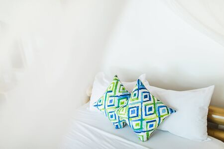 Two colorful blue and green ornamental pillows on white bed. Light cozy interior design. Empty place.