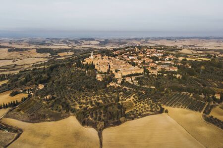 Aerial panoramic drone view of Pienza old town in Tuscany, Italy. San Quirico dOrcia region. Olive gardens and agriculture fields around. Autumn view. Banco de Imagens